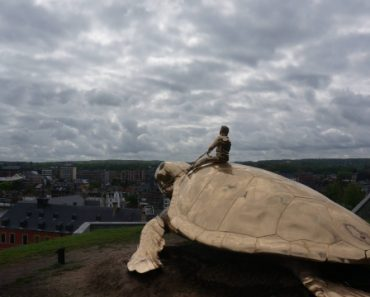 This golden statue of Elvis driving a sea turtle on a fort above a city in Blegium